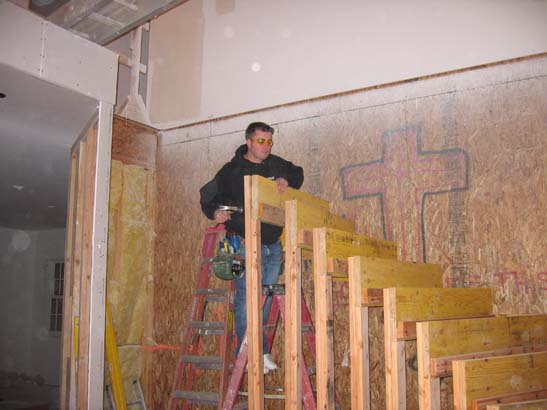 Before photo of a worker standing on a ladder next to a frame of stairs, with a graffitid wall behind him.