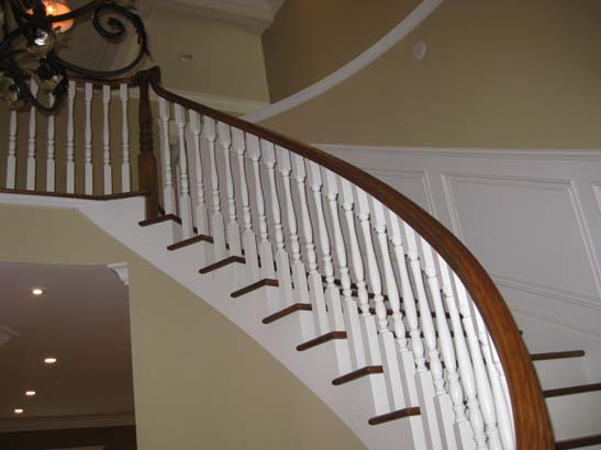 After photo of the finished product - white stairs with deep brown steps and a white trimmed wall behind it.