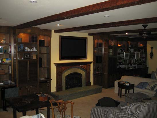 After photo of a cherrywood paneled gas fireplace with green marbel mantel.